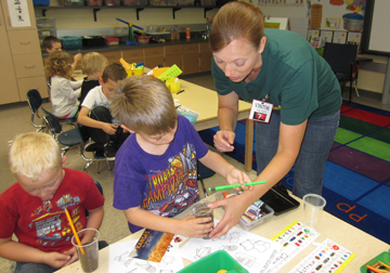 Children at Wamego Elementary School plant tiny seeds of wheat in order to learn how plants grow and become food.